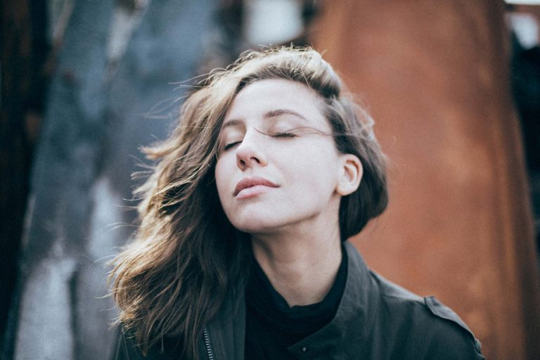 Person with closed eyes taking a deep breath