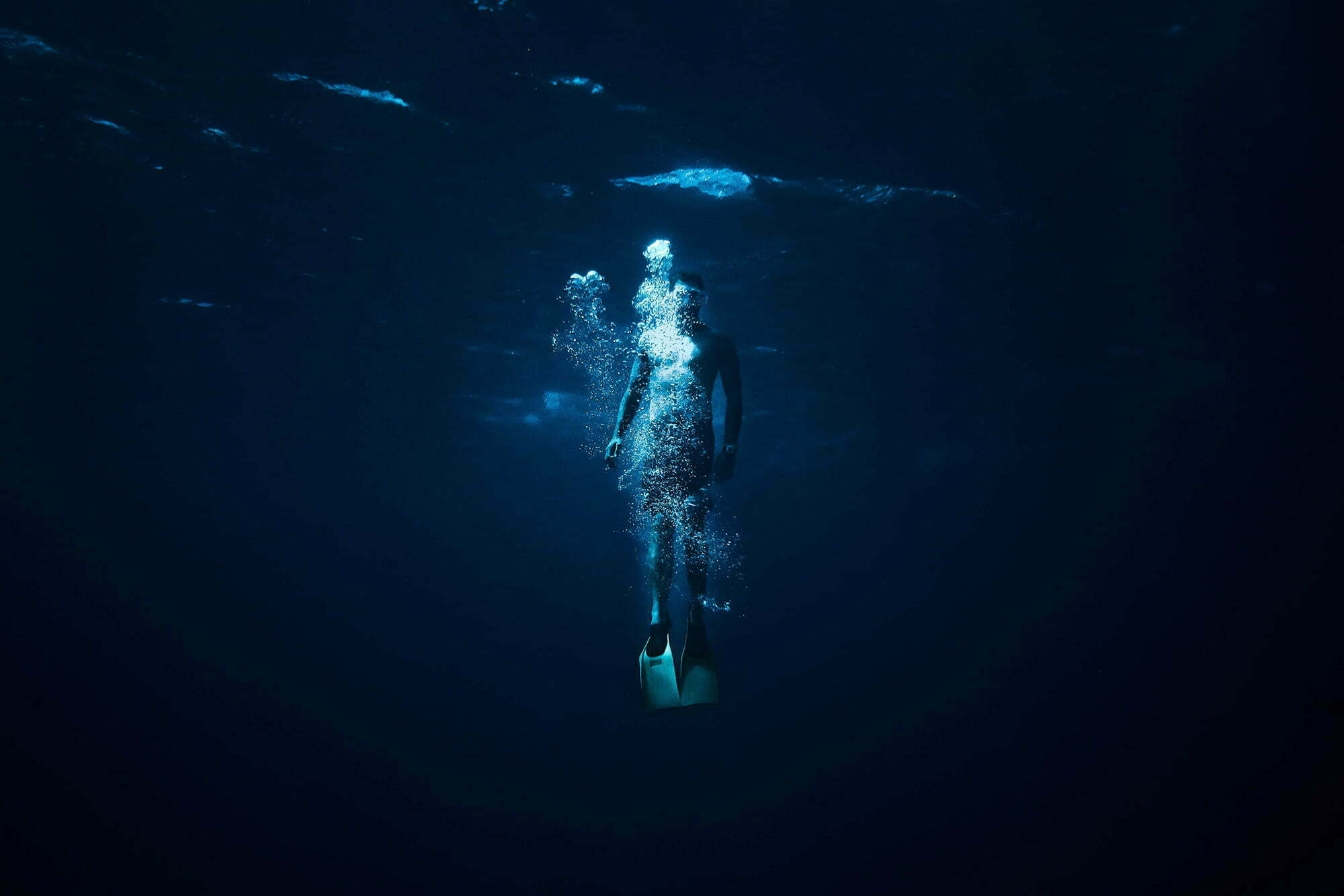 Person resurfacing from a dive in dark blue ocean water to take a breath