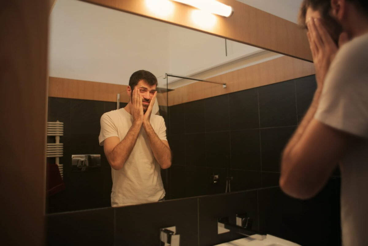 Person looking at themselves in a mirror with a feeling of anxiety and stress