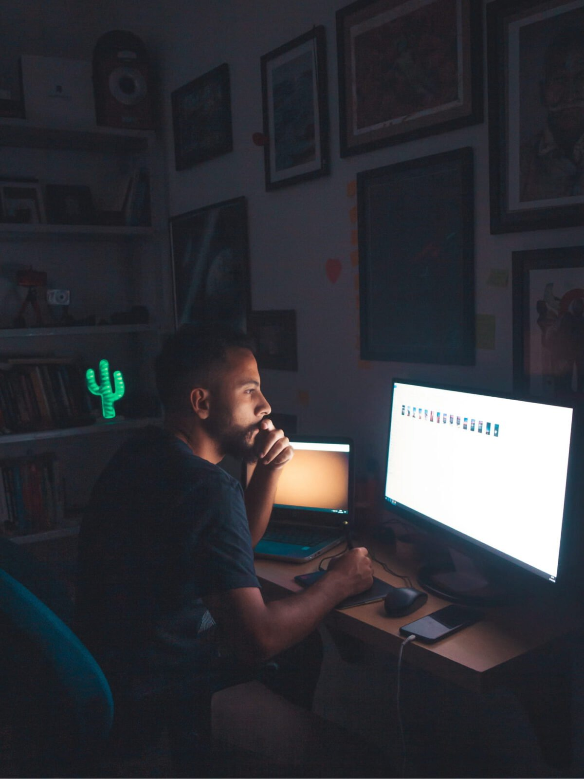 A person sitting in the dark in front of a screen looking at images.