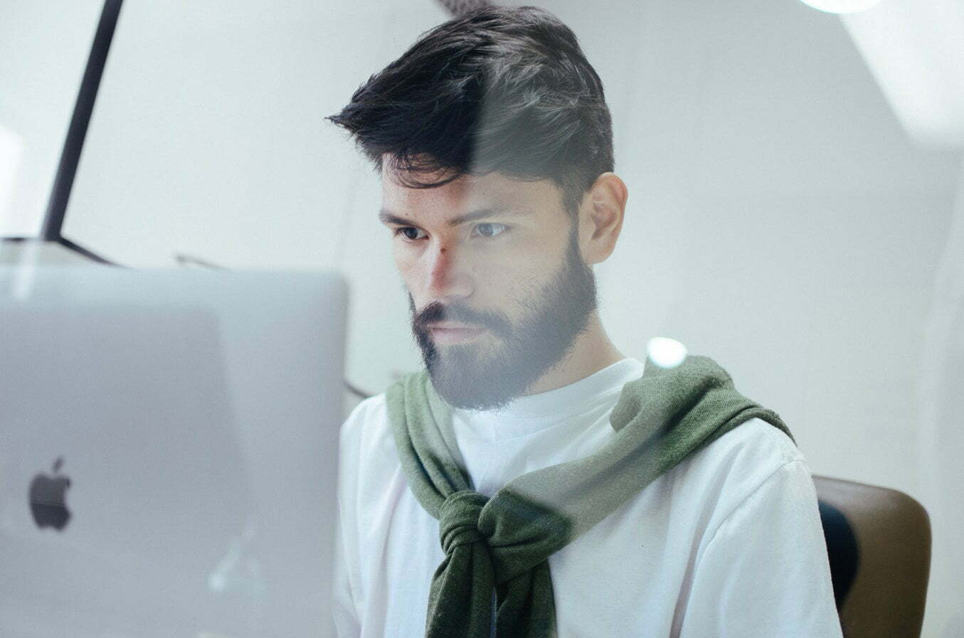 A person in a white shirt with a green sweater over his shoulders working with deep focus while looking at an Apple Screen