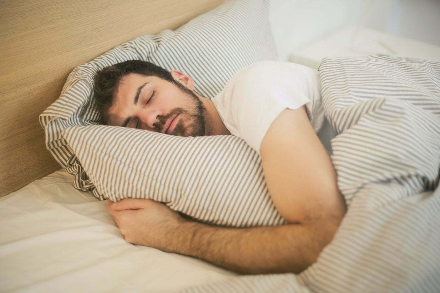 a person in a white shirt sleeping in bed