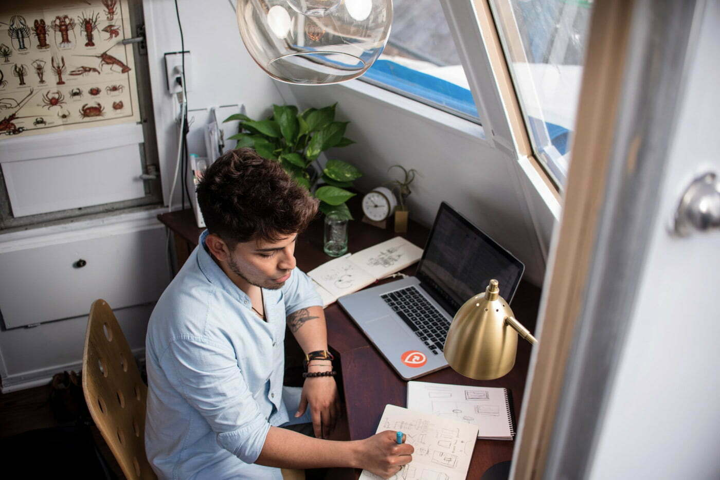 A person in a blue shirt sitting at a desk in front of a laptop writing something in his notebook.